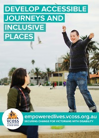 A boy with down syndrome is standing up celebrating and laughing in St Kilda, while his carer watches on