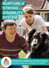 Woman with disability is in her front yard patting her dog while a carer watches on